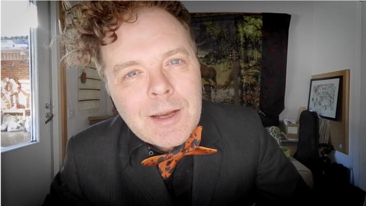 Jukka Takalo katsoo kameraan läheltä oranssi rusetti kaulassaan